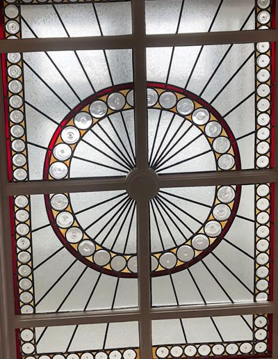 Sky light stained glass bevels and circular pieces meeting in the middle